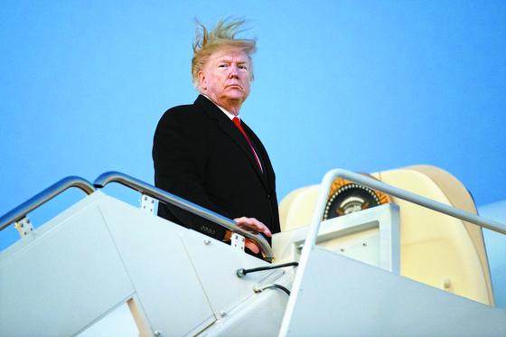 18일(현지시간) 미국 하원에서 탄핵소추안을 처리하던 시각, 도널드 트럼프 대통령이 미시간주에서 열리는 선거 유세를 위해 앤드루 공군기지에서 전용기에 오르고 있다. [AP=연합뉴스]