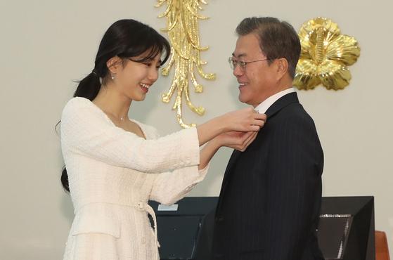 가수 수지가 20일 청와대에서 열린 사랑의 열매 전달식에서 문재인 대통령에게 뱃지를 옷깃에 달아주고 있다. 강정현 기자