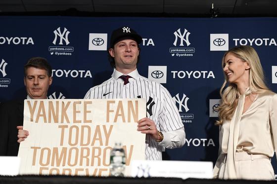 """게릿 콜은 지난 2001년 뉴욕 양키스와 애리조나 다이아몬드백스와 월드시리즈에 """"오늘도, 내일도, 영원히 양키스 팬""""이라고 적힌 피켓을 들고 양키스를 응원했다. 2019년 12월 양키스 입단식에서 당시 피켓을 재연해 들고 있는 콜. [로이터=연합뉴스]"""