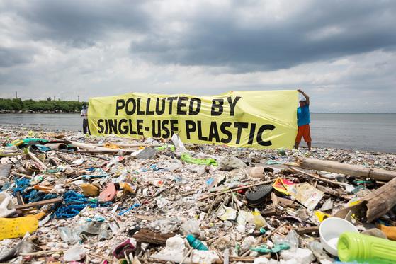 """필리핀 마닐라 해안에서 그린피스 활동가들이 '일회용 플라스틱으로 인한 오염""""이라고 적힌 플래카드를 펼치고 있다. [중앙포토]"""