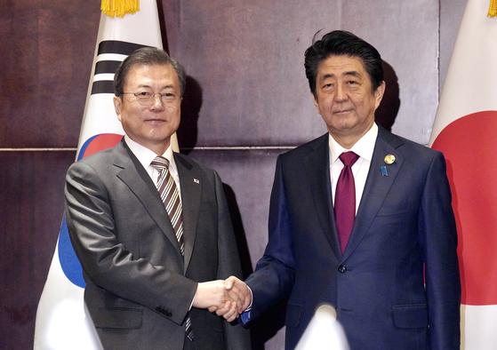 문재인 대통령이 24일 오후 중국 쓰촨성 청두에서 아베 신조 일본 총리를 만나 악수하고 있다. [청와대사진기자단]