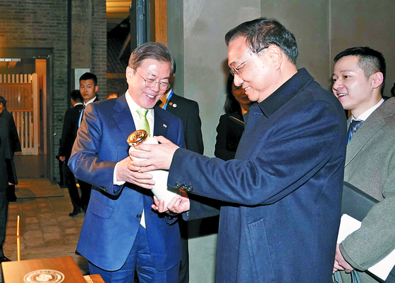 문재인 대통령이 23일 중국 쓰촨성 청두 수정방박물관에서 리커창 중국 총리로부터 특별 제작된 백주를 선물받고 있다. [청와대사진기자단]