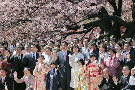 지난 4월 13일 일본 도쿄 신주쿠교엔에서 실시된 총리 주최 '벚꽃 보는 모임' 행사에서 아베 신조 총리와 부인 아키에 여사가 참석자들과 기념촬영을 하고 있다. [지지·AFP=연합뉴스]