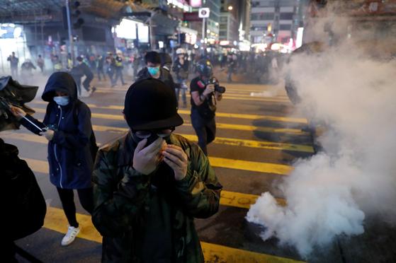 홍콩의 송환법 반대 시위가 크리스마스 이브인 24일(현지시간) 밤 침사추이 거리에서 열렸다. 시위대가 경찰이 쏜 최루가스를 피해 달아나고 있다. [로이터=연합뉴스]
