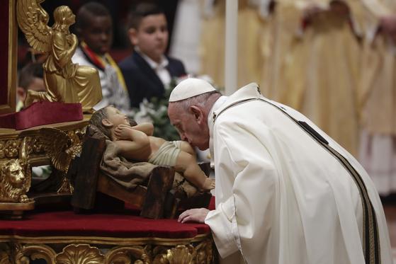 프란치스코 교황이 24일 성탄 전야 미사에서 아기예수 조각상에 입을 맞추고 있다. [AP=연합뉴스]