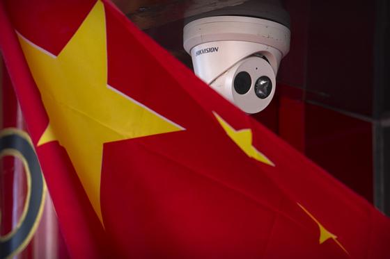 중국 당국과 공안경찰이 안면인식 기술 등을 활용해 개인정보를 적극적으로 무단 수집하고 있다고 NYT가 보도했다. 사진은 중국 오성홍기 뒤의 폐쇄회로(CC)TV. [AP=연합뉴스]