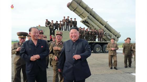 북한이 지난 8월 24일 '새로 연구 개발한 초대형 방사포'를 김정은 국무위원장의 지도 하에 성공적으로 시험발사했다고 북한 매체들이 8월 25일 보도했다. 조선중앙TV가 25일 오후 공개한 사진에서 김 위원장이 방사포를 뒤로 하고 활짝 웃고 있다. [연합뉴스]