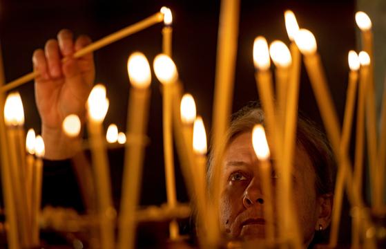 25일 불가리아 소피아에 있는 세인트 알렉산더 넵스키 성당에서 염원을 담은 성탄 촛불을 켜고 있다. [EPA=연합뉴스]