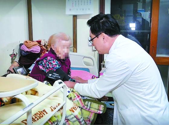 서울 노원구 파티마의원 장현재 원장이 환자 집을 방문해 왕진을 하고 있다. 혈압과 혈당을 재고, 식사를 잘 하는지를 체크하고, 혈액을 채취했다.[사진 장현재]