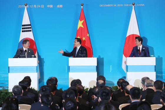 한·중·일 정상회담을 마친 리커창 중국 총리가 24일(현지시간) 쓰촨성 청두 세기성 국제회의센터에서 공동언론발표를 하고 있다. 왼쪽부터 문재인 대통령, 리 총리, 아베 신조 일본 총리. [청와대사진기자단]