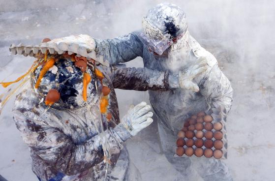 스페인 앨리칸네 이비 마을에서 28일(현지시간) 열린 '엘센파리나츠' 축제 참가자가 다른 참가자에게 계란 공격을 하고 있다. [AP=연합뉴스]