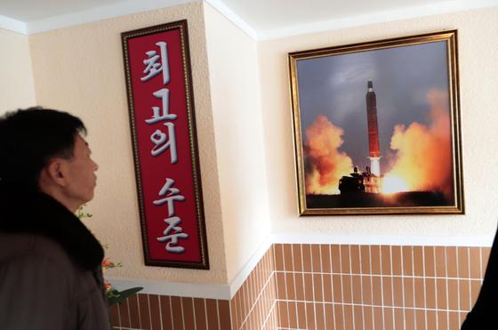 지난 11월 26일 북한 평양의 한 공장 기숙사에 걸린 북한의 미사일 발사 사진을 한 남자가 보고 있다. [AP=연합뉴스]