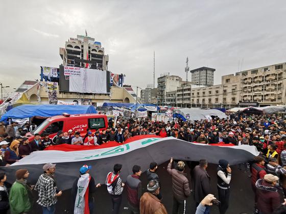 이라크 반정부 시위대가 27일 수도 바그다드 도심에서 대형 이라크 국기를 옮기며 시위를 벌이고 있다. [로이터=연합뉴스]