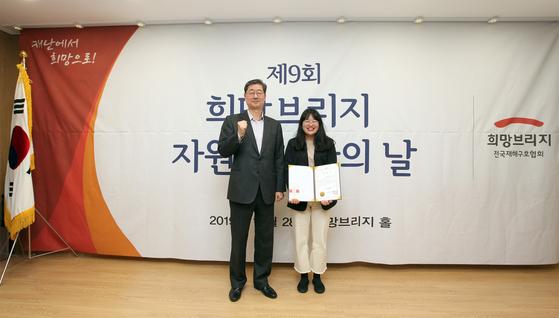 희망브리지 전국재해구호협회 송필호 회장이 2019 자원봉사 대상을 받은 김수진 씨에게 상장 및 부상을 수여했다.