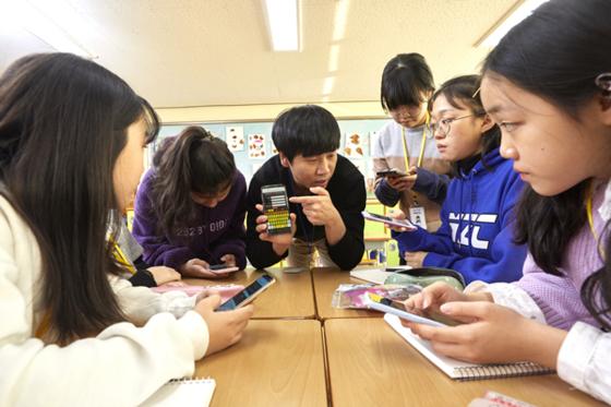 박준호 교사가 소중 학생기자단에게 모바일 영상 편집 애플리케이션 키네마스터의 이용법을 설명하고 있다. 박 교사의 지시에 따라 학생기자단이 애플리케이션을 설치 후 필요한 자격을 갖추고 있다.