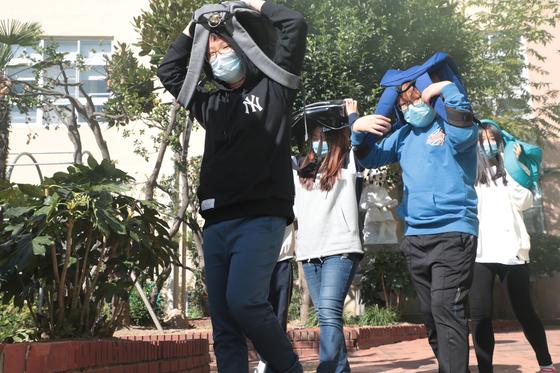 지난해 10월 30일 부산 서구 송도초등학교에서 열린 복합재난 대응훈련. 지진경보가 울리자 4~6학년 200여 명의 학생들이 신속하게 대피하고 있다. [중앙포토]