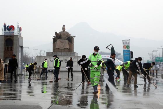 초미세먼지 주의보가 발령된 지난 3월 20일 오전 서울 광화문광장에서 서울시·종로구 관계자와 주민들이 물청소를 하고 있다. 자동차 배기가스뿐만 아니라 자동차 타이어 마모 때 나오는 먼지도 도시 대기오염 원인으로 지목되고 있다. [뉴스1]