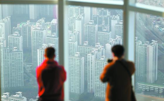 서울 송파구 잠실 롯데월드타워를 방문한 사람들이 어두운 하늘을 바라보고 있다. [연합뉴스]