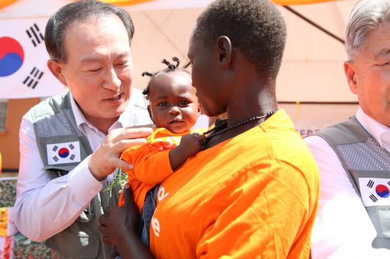 지난 11일 우간다에서 열린 산모 병동 완공식에서 김천수(왼쪽) 굿피플 회장이 아기와 엄마를 보살피고 있다. 굿피플은 2011년 우간다 지부를 설립해 보건의료와 교육지원사업을 진행하고 있다. [사진 굿피플]