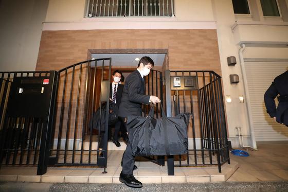 일본 도쿄지검 관계자가 2일 도쿄 미나토구에 있는 카를로스 곤 전 닛산회장의 집을 수사한 뒤 밖으로 나오고 있다. [지지통신=연합뉴스]