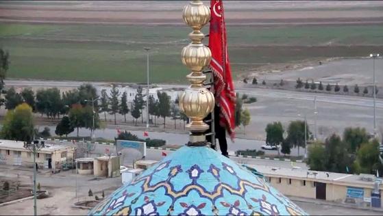사아파 민병대원이 피의 복수를 상징하는 붉은 깃발을 이란 잠카란 이슬람사원에 게양하고 있다. [이란 국영TV 캡처]