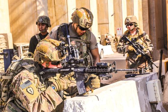 """친이란 시위대 수천 명이 이라크 수도 바그다드의 미국대사관을 포위한 채 """"미국 반대"""" """"트럼프 반대"""" """"미국에 죽음을!"""" 등의 구호를 외쳤다. 시위대는 대사관 외벽과 감시초소에 불을 지르고, 차량 출입문과 감시 카메라를 부쉈다. 사진은 지난달 31일(현지시간) 이라크 바그다드 미 대사관 인근 전진기지에서 미군 병사들이 방어 태세를 취하고 있는 모습. [로이터=연합뉴스]"""