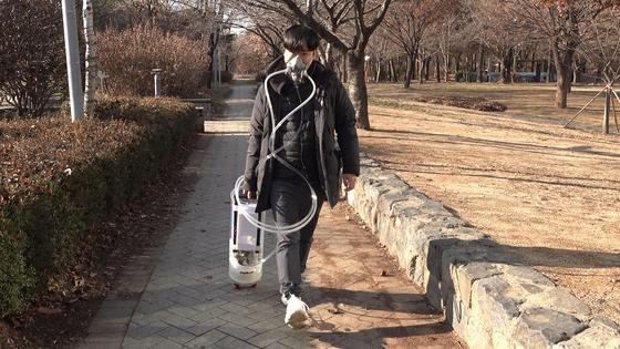긱블이 자체 제작한 공기청정 캐리어 마스크를 착용하고 거리를 걷고 있다. [사진 왕준열]