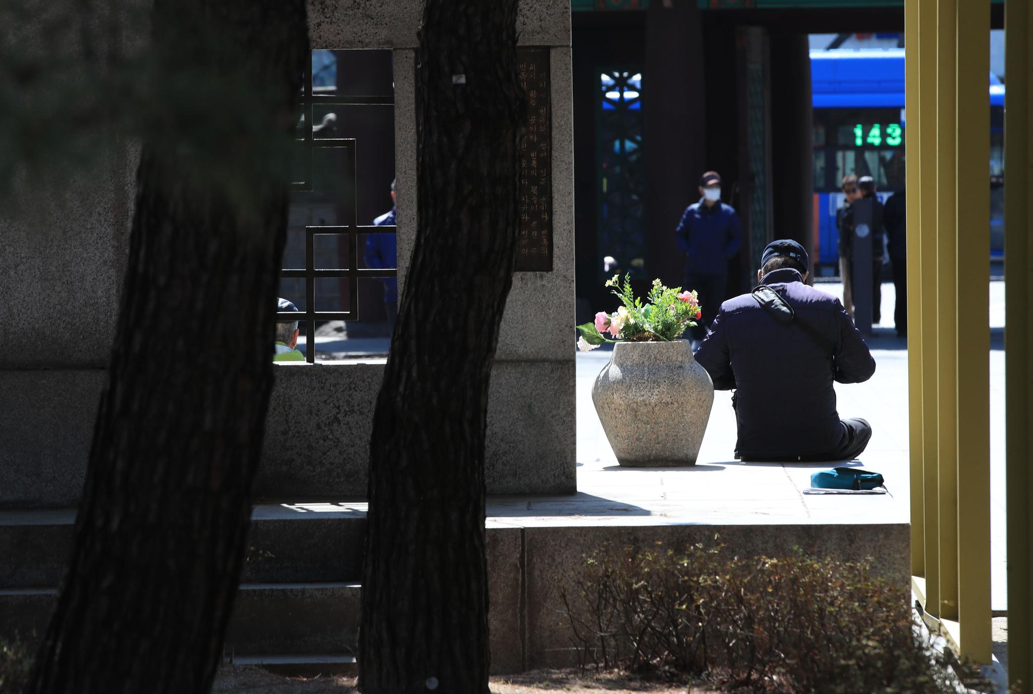 서울 종로구 탑골공원 앞에 앉아있는 한 중장년 남성. [연합뉴스]