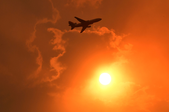 4일 호주 남쪽 나우라 지역 상공에 뜬 비행기가 방화 물질을 뿌리고 있다. 호주 남동주 지역의 계속되는 산불로 일부 지역의 하늘이 빨갛게 물들었다. [로이터=연합뉴스]