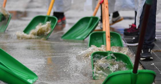 7일 강원 화천군 산천어축제장에서 겨울비가 내리자 축제 관계자들이 빗물 제거작업을 벌이고 있다. [화천군 제공=연합뉴스]