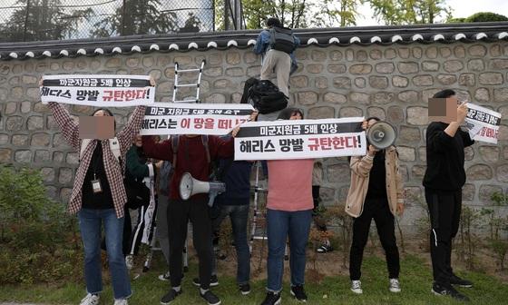 한국대학생진보연합 소속 대학생이 지난해 10월 18일 오후 서울 중구 주한 미국대사관저에서 방위비분담금 협상 관련 기습 농성을 하기 위해 담벼락을 넘고 있다. [뉴시스]