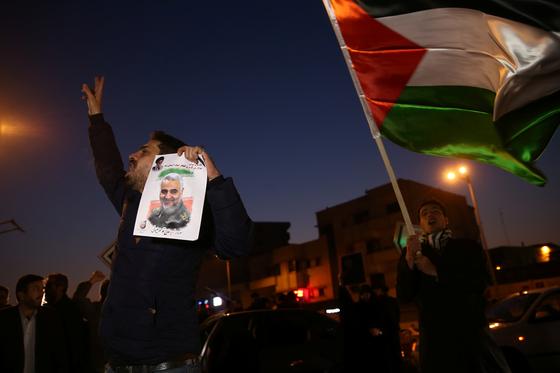 8일(현지시간) 이란이 이라크 내 미군 기지를 공격했다는 소식을 접한 테헤란 시민들이 자축하기 위해 거리로 뛰쳐나왔다. 한 남성이 미군 공습에 사망한 거셈 솔레이마니 쿠드스군 총사령관의 얼굴 사진을 들고 환호하고 있다. [로이터=연합뉴스]