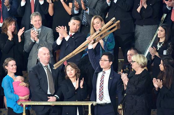 지난 2018년 1월 30일 도널드 트럼프 미 대통령의 첫 국정연설에 참석한 탈북민 지성호씨가 목발을 머리 위로 들어보이고 있다. [중앙포토]