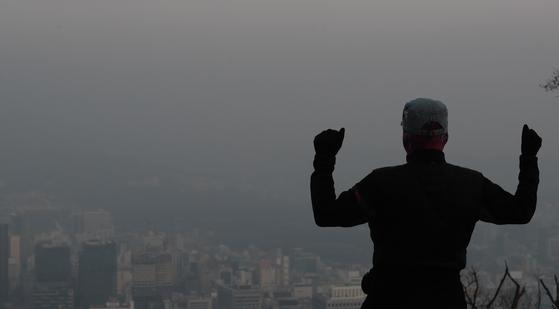 한 시민이 미세먼지와 초미세먼지가 나쁨 상태를 보인 10일 오전 서울 용산구 남산공원에서 뿌연 도심을 바라보고 있다. [뉴시스]