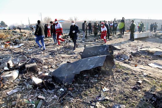 8일(현지시간) 추락한 우크라이나 항공기 사고 현장에서 응급구조대원들이 사고기의 잔해 주변을 수색하고 있다. [EPA=연합뉴스]