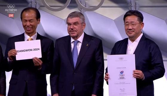 국제올림픽위원회는 10일 스위스 로잔에서 총회를 열어 강원도를 2024년 동계청소년올림픽 개최지로 확정했다. 최문순 강원도지사(왼쪽)가 동계청소년올림픽 유치에 성공한 뒤 기뻐하고 있다. 오른쪽은 토마스 바흐 IOC 위원장과 박양우 문화체육관광부 장관. [사진 강원도 제공]