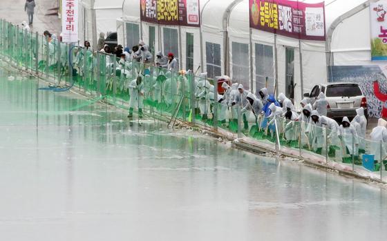 겨울비가 내린 지난 7일 오전 강원 화천군 산천어축제장에서 공무원들이 얼음낚시터 행사장으로 흘러 들어가는 빗물을 퍼내고 있다. [연합뉴스]