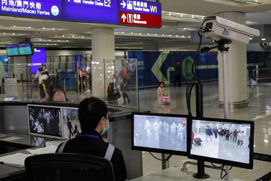 홍콩 국제공항의 검역 담당자가 4일 모니터를 통해 입국장으로 들어오는 여행자들을 지켜보고 있다. 홍콩에서는 폐렴 증상을 보이는 15명의 환자가 나왔다. [AP=연합뉴스]