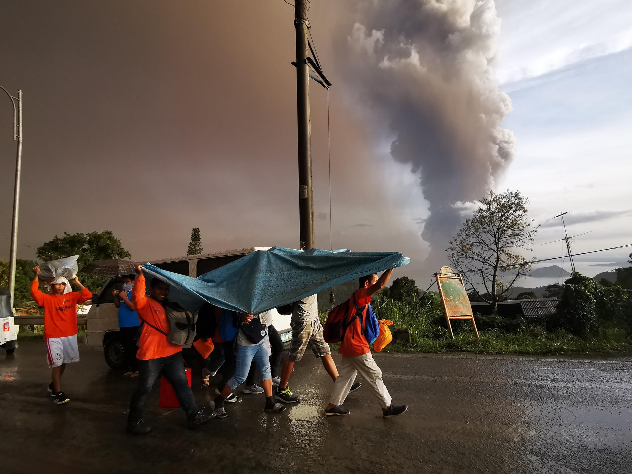 12일(현지시간) 필리핀 따가이따이 인근 지역의 따알 화산이 재를 내 뿜고 있는 가운데 주민들이 대피하고 있다. [EPA=연합뉴스]