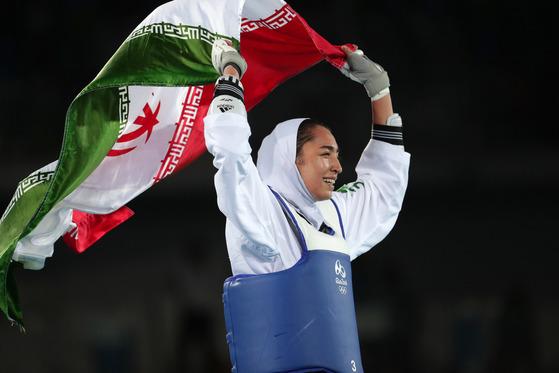 망명을 선언한 이란의 여성 태권도 선수 알리자데가 2016년 리우 올림픽에서 동메달을 딴 이후 국기를 들고 기뻐하고 있다. [중앙포토]
