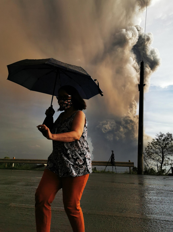 12일(현지시간) 필리핀 따가이따이 인근 지역의 따알 화산이 재를 내 뿜고 있는 가운데 한 주민이 우산을 쓰고 대피하고 있다. [EPA=연합뉴스]