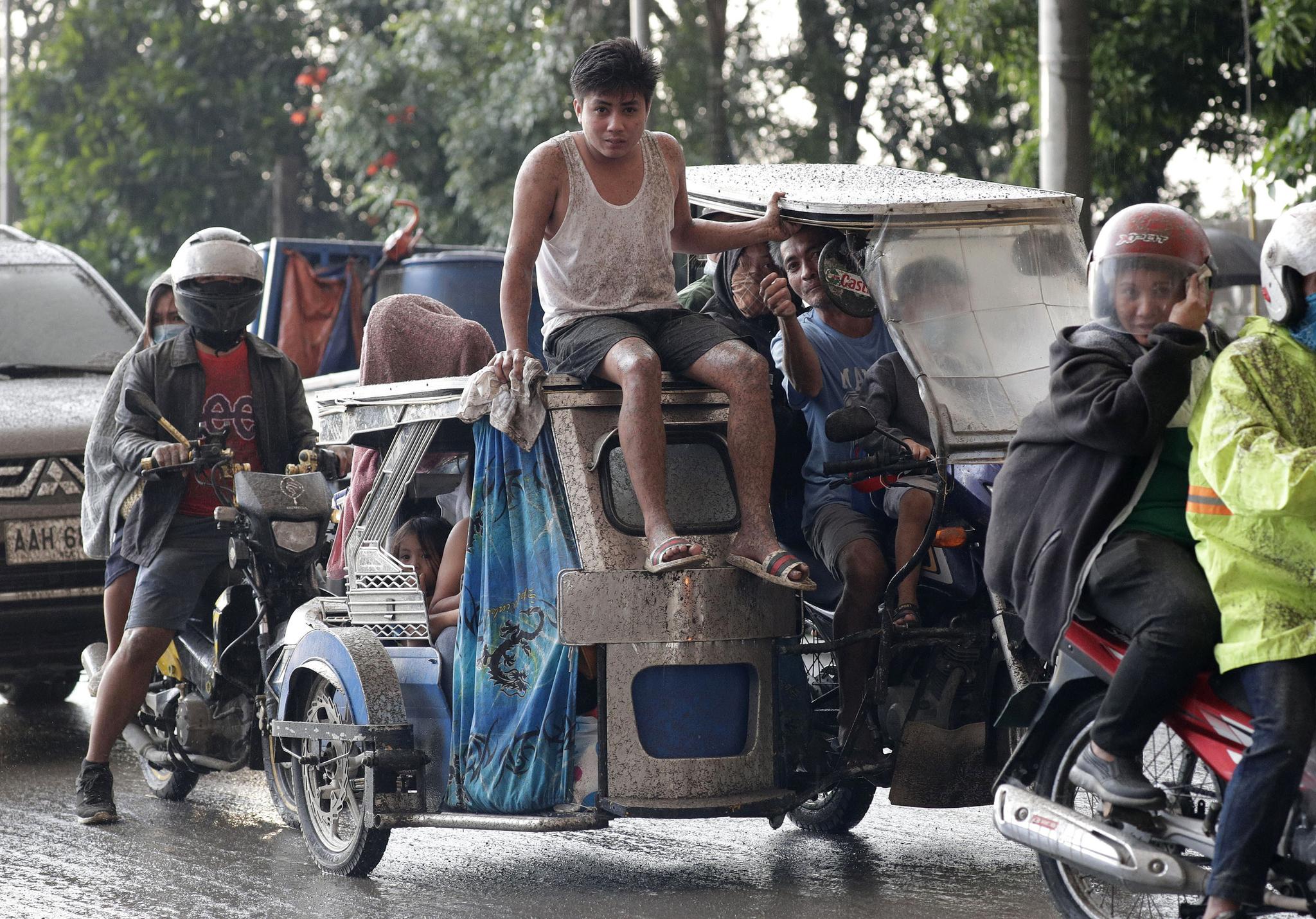 12일(현지시간) 필리핀 따가이따이 인근 지역의 따알 화산이 재를 내 뿜고 있는 가운데 주민들이 대피하고 있다. [AP=연합뉴스]