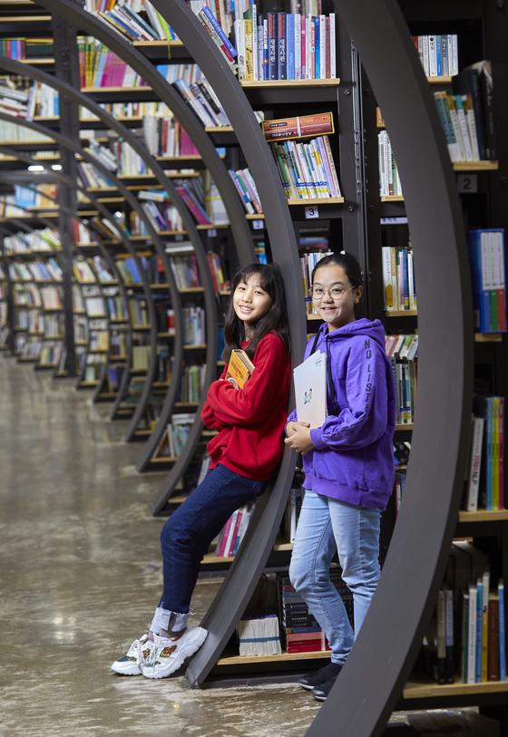 터널처럼 둥근 통로 양옆으로 책이 가득 꽂힌 책꽂이는 SNS에 '인증샷'이 자주 올라오는 서울책보고의 유명한 포토스팟이다. 정해린(왼쪽)·김은비 학생기자가 책꽂이에 기대 포즈를 취했다.
