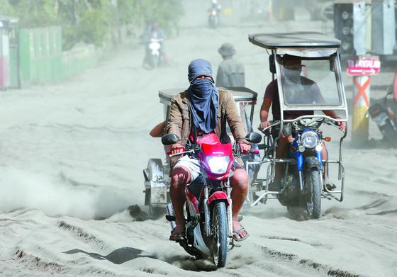 탈 화산 폭발로 분출된 화산재가 도로를 덮은 바탕가스주 아곤실로에서 사람들이 13일 오토바이로 이동하고 있다. [EPA=연합뉴스]