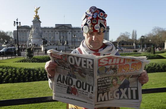 영국 왕실의 '빅팬'을 자처하는 존 로그리가 9일 영국 런던 버킹엄궁 앞에서 심각한 표정으로 '메그시트' 관련 신문 기사를 읽고 있다. [AP=연합뉴스]