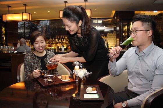 서울 웨스틴조선호텔의 티소믈리에 강다희(30, 가운데)씨가 비타민 블랙 티를 선보이고 있다. 오른쪽 남성이 마시는 차는 말차 플럼. [사진 웨스틴조선호텔]