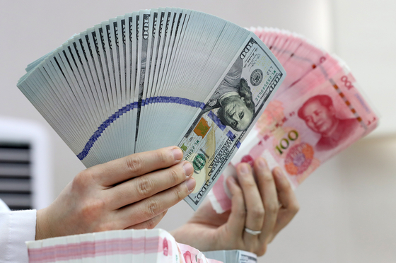 은행 직원이 미국 달러와 중국 위안화 지폐를 점검하고 있다. [뉴스1]