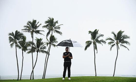 임성재가 4라운드 17번 홀에서 우산을 쓴 채 다른 선수의 샷을 기다리고 있다. 그는 이날 16번 홀 트리플 보기를 했다. [AFP=연합뉴스]