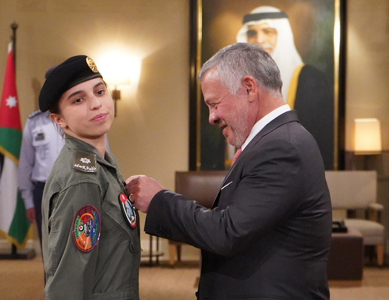 압둘라 2세 요르단 국왕이 8일(현지시간) 살마 공주에게 파일럿 윙을 달아주고 있다. [EPA=연합뉴스]