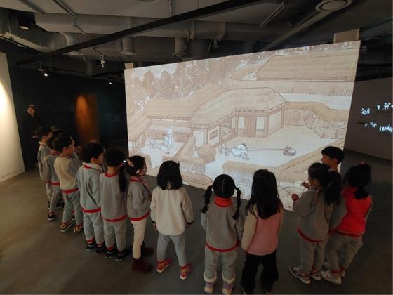 어린아이들이 김홍도 풍속도 애니메이션을 보며 옛사람들의 땀이 담긴 향토민요를 듣고 있다.[사진 서울우리소리박물괃]